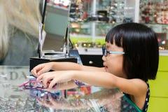 Ασιάτης λίγο κινεζικό κορίτσι που επιλέγει τα γυαλιά Στοκ Φωτογραφία