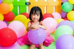 Ασιάτης λίγο κινεζικό κορίτσι που παίζει με τα ζωηρόχρωμα μπαλόνια Στοκ εικόνα με δικαίωμα ελεύθερης χρήσης