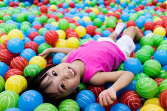 Ασιάτης λίγο κινεζικό κορίτσι που παίζει με τις ζωηρόχρωμες πλαστικές σφαίρες Στοκ εικόνα με δικαίωμα ελεύθερης χρήσης