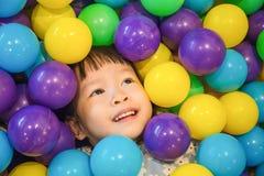 Ασιάτης λίγο κινεζικό κορίτσι που παίζει με τις ζωηρόχρωμες πλαστικές σφαίρες Στοκ εικόνες με δικαίωμα ελεύθερης χρήσης