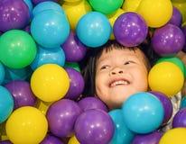 Ασιάτης λίγο κινεζικό κορίτσι που παίζει με τις ζωηρόχρωμες πλαστικές σφαίρες Στοκ φωτογραφία με δικαίωμα ελεύθερης χρήσης