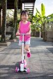 Ασιάτης λίγο κινεζικό κορίτσι που παίζει με το μηχανικό δίκυκλο Στοκ εικόνες με δικαίωμα ελεύθερης χρήσης