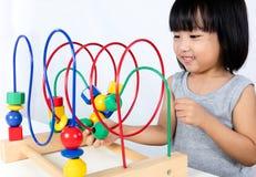 Ασιάτης λίγο κινεζικό κορίτσι που παίζει το ζωηρόχρωμο εκπαιδευτικό παιχνίδι Στοκ Εικόνες