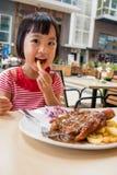 Ασιάτης λίγο κινεζικό κορίτσι που τρώει τα δυτικά τρόφιμα Στοκ Εικόνες