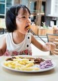Ασιάτης λίγο κινεζικό κορίτσι που τρώει τα δυτικά τρόφιμα Στοκ φωτογραφία με δικαίωμα ελεύθερης χρήσης
