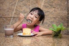 Ασιάτης λίγο κινεζικό κορίτσι που τρώει το εύγευστο κέικ Στοκ Φωτογραφία