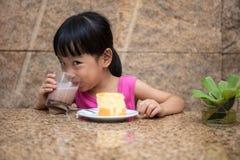 Ασιάτης λίγο κινεζικό κορίτσι που τρώει το εύγευστο κέικ Στοκ Εικόνα