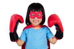 Ασιάτης λίγο κινεζικό κορίτσι που φορά το έξοχο κοστούμι ηρώων με τον εγκιβωτισμό Στοκ φωτογραφία με δικαίωμα ελεύθερης χρήσης