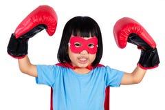 Ασιάτης λίγο κινεζικό κορίτσι που φορά το έξοχο κοστούμι ηρώων με τον εγκιβωτισμό Στοκ Εικόνα
