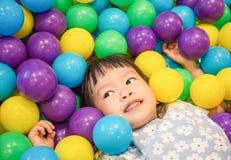 Ασιάτης λίγο κινεζικό κορίτσι που παίζει με τις ζωηρόχρωμες πλαστικές σφαίρες Στοκ Εικόνες
