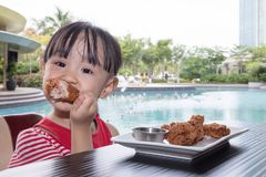 Ασιάτης λίγο κινεζικό κορίτσι που τρώει το τηγανισμένο κοτόπουλο Στοκ εικόνα με δικαίωμα ελεύθερης χρήσης