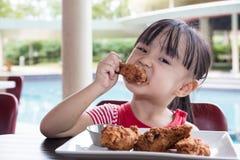 Ασιάτης λίγο κινεζικό κορίτσι που τρώει το τηγανισμένο κοτόπουλο Στοκ Εικόνες