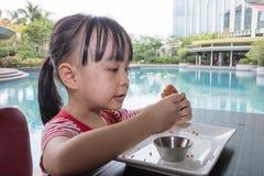 Ασιάτης λίγο κινεζικό κορίτσι που τρώει το τηγανισμένο κοτόπουλο Στοκ Εικόνα