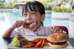 Ασιάτης λίγο κινεζικό κορίτσι που τρώει Burger και το τηγανισμένο κοτόπουλο Στοκ εικόνες με δικαίωμα ελεύθερης χρήσης