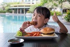 Ασιάτης λίγο κινεζικό κορίτσι που τρώει Burger και το τηγανισμένο κοτόπουλο Στοκ Εικόνα