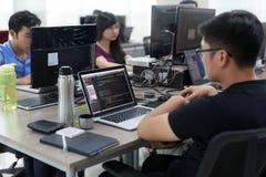 Ασιάτης μεταφέρει τη συνεδρίαση ομάδας υπεύθυνων για την ανάπτυξη στο λειτουργώντας lap-top γραφείων Στοκ Εικόνες