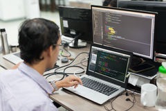 Ασιάτης μεταφέρει το προγραμματιστή λογισμικού που εξετάζει συνεδρίαση οθόνης το γραφείο Στοκ Φωτογραφίες