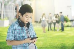 Ασιάτης ο μαθητής που φαίνεται το smartphone του στοκ φωτογραφίες