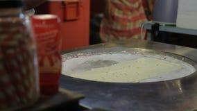 Ασιάτης προετοιμάζει ένα κρύο επιδόρπιο σε μια επιφάνεια μετάλλων στην κουζίνα απόθεμα βίντεο