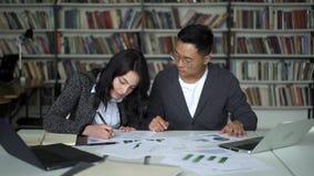 Ασιατικά άτομο και θηλυκό ζευγών που εργάζονται στο πρόγραμμα στη βιβλιοθήκη απόθεμα βίντεο