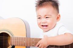 Ασιατικά αγόρια παιδιών πορτρέτου 1 έτος 6 μήνες που παίζουν την κιθάρα στοκ φωτογραφία με δικαίωμα ελεύθερης χρήσης
