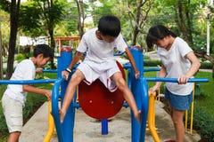Ασιατικά αγόρι και κορίτσι workout στο φραγμό εμβύθισης Στοκ Εικόνες