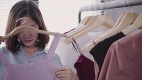 Ασιατικά ενδύματα αγορών γυναικών Αγοραστής που εξετάζει τον ιματισμό στη ράγα στο εσωτερικό στο κατάστημα ιματισμού απόθεμα βίντεο