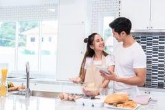 Ασιατικά ζεύγη που μαγειρεύουν και που ψήνουν το κέικ μαζί στην αίθουσα α κουζινών στοκ εικόνα