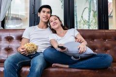 Ασιατικά ζεύγη που προσέχουν την τηλεόραση και που τρώνε popcorn μαζί επάνω στοκ φωτογραφία