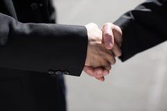 Ασιατικά και καυκάσια χέρια τινάγματος επιχειρηματιών Στοκ Φωτογραφία