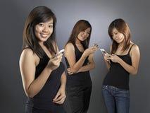 ασιατικά κινεζικά κινητά τηλέφωνα κοριτσιών η χρησιμοποίησή τους Στοκ Εικόνες