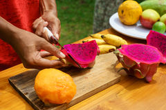 Ασιατικά κοριτσιών φρούτα δράκων φλούδας κόκκινα, Ινδονησία, Μπαλί Στοκ Εικόνα