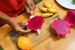Ασιατικά κοριτσιών φρούτα δράκων φλούδας κόκκινα, Ινδονησία, Μπαλί Στοκ φωτογραφία με δικαίωμα ελεύθερης χρήσης