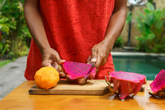 Ασιατικά κοριτσιών φρούτα δράκων φλούδας κόκκινα, Ινδονησία, Μπαλί Στοκ Εικόνες