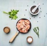Ασιατικά μαγειρεύοντας συστατικά με τις φρέσκες μικρές γαρίδες σε ένα μικρό τηγανίζοντας τηγάνι, χορτάρια και μια ξύλινη μπλε τοπ Στοκ εικόνα με δικαίωμα ελεύθερης χρήσης
