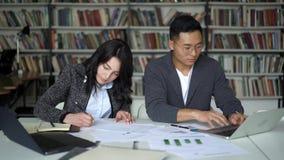 Ασιατικά νέα άτομο και θηλυκό ζευγών που εργάζονται στο πρόγραμμα στη βιβλιοθήκη απόθεμα βίντεο