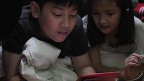 Ασιατικά παιδιά που παίζουν με μια ταμπλέτα cpmputer στο σπίτι Καταγραμμένος φορητός σε σε αργή κίνηση σε 4K σε 60fps απόθεμα βίντεο