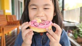 Ασιατικά παιδιά που τρώνε τα γλυκά donuts απόθεμα βίντεο