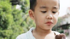 Ασιατικά παιδιά που τρώνε το παγωτό σοκολάτας με τη συγκίνηση ευτυχίας απόθεμα βίντεο