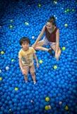 Ασιατικά παιχνίδια μικρών παιδιών σε μια ομάδα των σφαιρών Στοκ Εικόνες