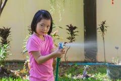 Ασιατικά παιδιά που παίζουν στον κήπο και που παίρνουν υγρά με τη μάνικα Στοκ εικόνες με δικαίωμα ελεύθερης χρήσης