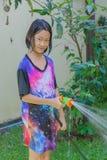 Ασιατικά παιδιά που παίζουν στον κήπο και που παίρνουν υγρά με τη μάνικα Στοκ φωτογραφία με δικαίωμα ελεύθερης χρήσης