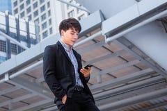 Ασιατικά στάση επιχειρησιακών ατόμων και smartphone χρήσης με το επιχειρησιακό bui Στοκ φωτογραφία με δικαίωμα ελεύθερης χρήσης