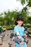Ασιατικά ταΐζοντας περιστέρια παιδιών στοκ εικόνα με δικαίωμα ελεύθερης χρήσης