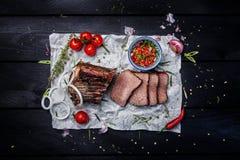 ασιατικά τρόφιμα Καπνισμένο κρέας με τη σάλτσα και τα χορτάρια ντοματών Ξύλινο σκοτεινό υπόβαθρο Τοπ όψη Στοκ Φωτογραφίες