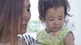 Ασιατικά τρόφιμα σίτισης μητέρων για την κόρη της στο σπίτι με το πρόσωπο χαμόγελου, ευτυχής ασιατική οικογενειακή έννοια απόθεμα βίντεο