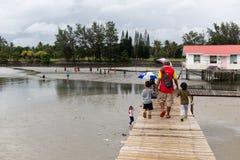 Ασιατικά χέρια παιδιών ` s εκμετάλλευσης πατέρων που περπατούν επάνω από το θαλάσσιο περίπατο στοκ εικόνες