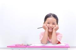 Ασιατικά χέρια συνεδρίασης μικρών κοριτσιών χαμόγελου στο πηγούνι με το μολύβι χρώματος Στοκ φωτογραφία με δικαίωμα ελεύθερης χρήσης