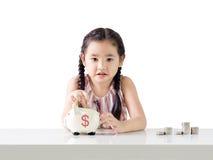 Ασιατικά χρήματα αποταμίευσης μικρών κοριτσιών σε μια piggy τράπεζα η ανασκόπηση απομόνωσε το λευκό Στοκ φωτογραφίες με δικαίωμα ελεύθερης χρήσης
