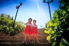 Ασιατικά όμορφα κορίτσια στα φορέματα διακοπών στα πέτρινα βήματα από τις εγκαταστάσεις Στοκ φωτογραφίες με δικαίωμα ελεύθερης χρήσης